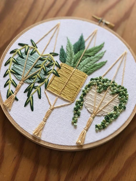 This 6 inch wooden hoop features a trio of hanging plants . Each one hanging in a hand stitched plant hanger , check out those tassels ! This is a made to order item and as such placement of leaves may vary slightly . The design really pops out from the hoop , I just love the