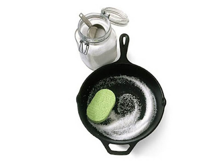 To clean a cast iron skillet, or a potjie pot, toss about 1/2 cup coarse salt into the pan and rub with a soft sponge. The salt removes excess oils and takes off the bits of food without messing with the seasoning of the pan. http://www.facebook.com/Alejen7IsCompletelyClean