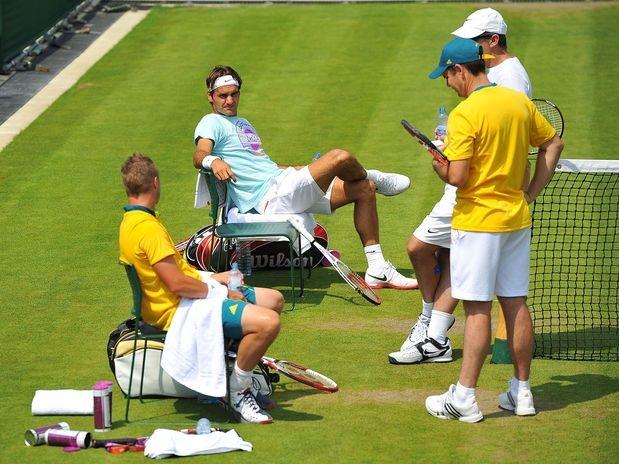 Roger Federer compareceu à quadra três do All England Lawn Tennis Club para treinar  na última quarta-feira. Sob um forte sol, que deixou o verão londrino com temperaturas superiores a 30º C, o suíço trabalhou com a companhia dos australianos Lleyton Hewitt e Bernard Tomic. Do lado de fora da quadra, fãs e curiosos se reuniram na arquibancada para ver o astro do tênis mundial  Foto: Bruno Santos/Terra