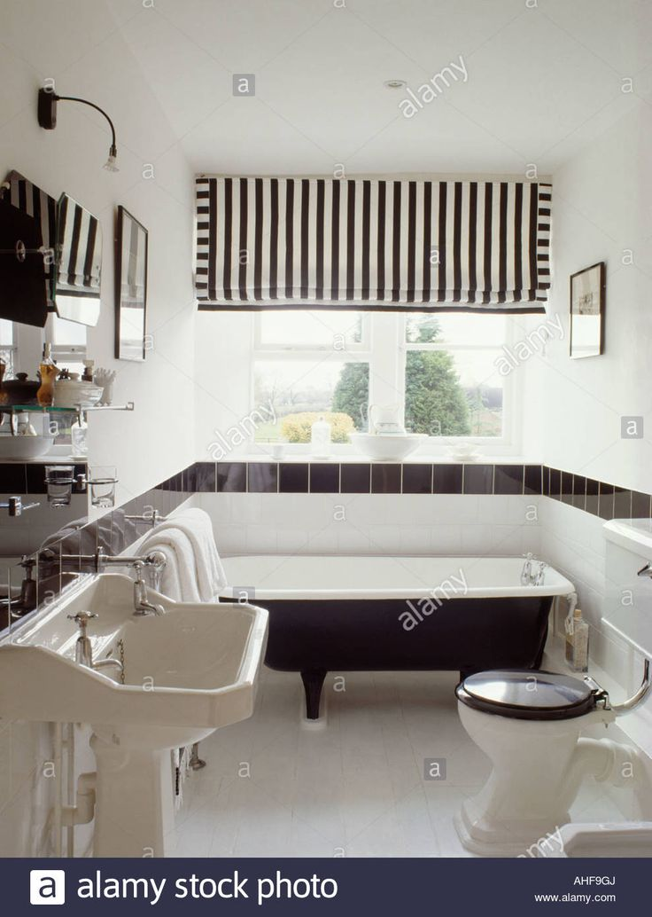 Black and white striped blind above rolltop bathtub in monochromatic modern bathroom with white pedestal basin Stock Photo