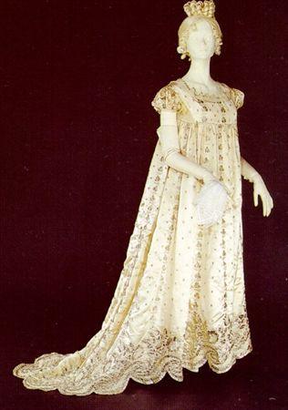 Vestido de cetim de seda branco-pérola bordado com lâmina de metal prateado formando motivos florais e vegetalistas. MatrizNet