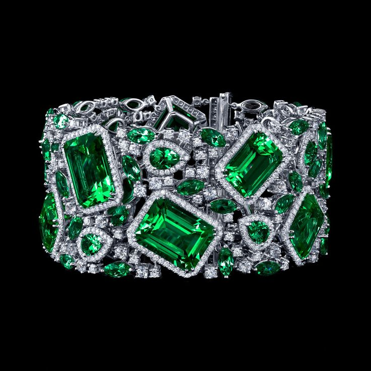 Robert PROCOP - Parisian Collection - Impressive Emerald and Diamond Deco Bracelet Celebration is defined in this elegant yet dazzling, Deco inspired Emerald and white Diamond cuff. Large emerald-cut Emerald are surrounded by brilliantly cut white Diamonds and interlaid with pear- cut Emerald bringing opulence of design and innovation to this piece. Each cut stone has been luxuriously framed with precision cut white Diamonds for a magnificent and glittering effect.