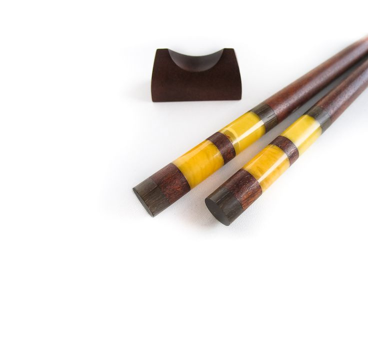 Chopsticks decorated with amber. Made of construction wood from the buildings of the Old Town of Gdansk, Poland. Black oak dating back to the 14th century.