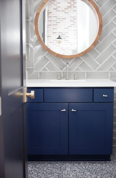 Blue and gray bathroom boasts a round mirror lining a glossy gray chevron tile backsplash placed above a bold blue washstand topped with white quartz alongside a gray penny tiled floor.