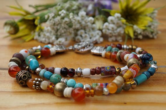 Three strand boho bracelet with assorted natural gemstones, glass and metal beads. Orange and blue highlights with silver toggle closure.
