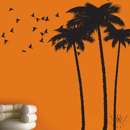 3 large black matte black palm tree wall stickers with a variety of small bird wall decals flying all placed on an orange wall above a white chair.