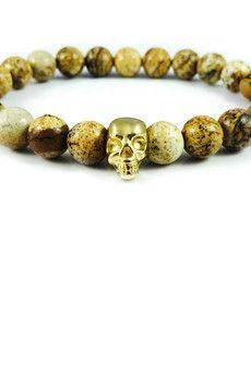 Dizarro to męska biżuteria najwyższej jakości produkowana z kamieni półszlachetnych, srebra, złota oraz kryształów Swarovski™.  Bransoletka wykonana z jaspisów pustynnych oraz czaszki pokrytej 23-karatowym, złotem. Szczegóły:- czaszka pokryta 23-karatowym, włoskim złotem- bransoletka wkładana na elastycznej gumce- średnica kulek: 8 mm- bransoletka zapakowana w eleganckie, czarne pudełko