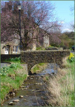 Downham village, Lancashire. Stone bridge, little brook, cottage in the background: lovely.