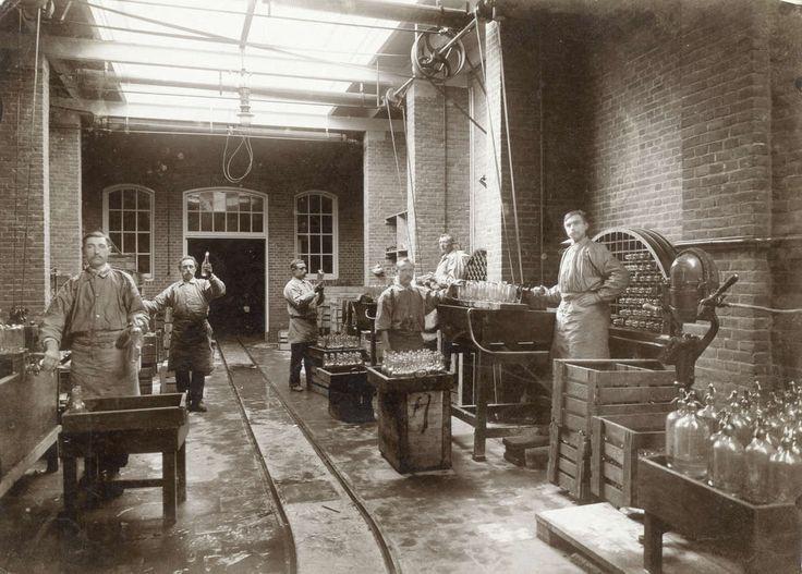 Limonadefabrieken. Het reinigen van de flessen met een flessenspoelmachine in de  Mineraalwaterfabriek G. Houweling in Amsterdam. Foto uit 1909.