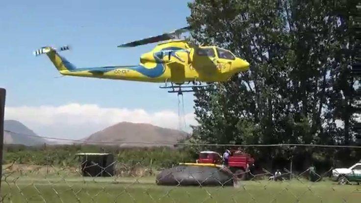 Helicópteros cargando agua desde la cancha del recreo Rinconada de Parra...