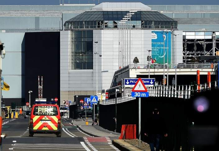 An airport fire brigade car is seen driving near the shattered glass facade of the departure hall at Brussels Airport in Zavedam
