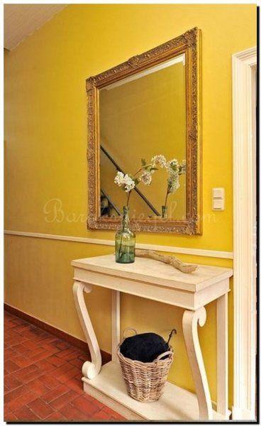 Ik hou van de gele kleur op de muur, De details maken het design met deze barokke spiegel boven een side table.
