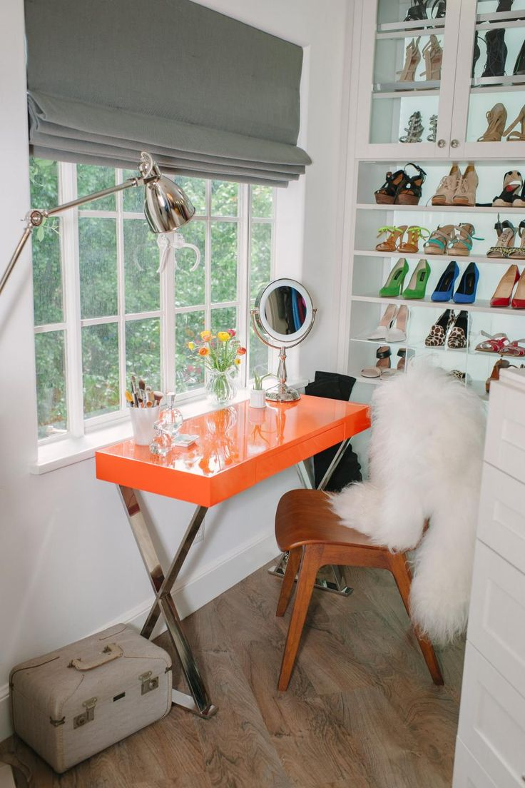 A lacquered orange desk and mid-century modern chair create a dressing area that's colorful and oh-so chic in the home of actress Tiffani Thiessen. A wall of custom storage houses an impressive shoe collection. Meanwhile, a white angora throw adds an extra splash of glamour.