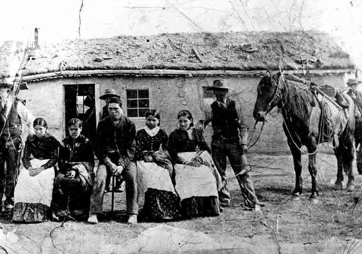 """Métis family at their winter cabin in Willow Bunch, Saskatchewan. Names and date unknown. Known as """"Hivernants"""" -- year-round, nomadic occupants of the northern Plains who hunted buffalo commercially in organized brigades, traded at posts down along the Missouri River, and settled in winter hamlets in wooded highland areas of the plains (as above) where there was wood, game, water and protection from blizzards. Courtesy of the PAHS Archives collection. JE"""
