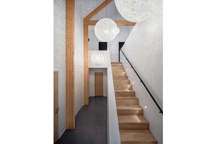 Eiken houten trap met zwart stalen leuninge ne gestucte balustrade. Dankzij de hoge houten spanten en de grote hoogte ontstaat een ruimtelijk effect. Royale en luxe entree!  Ontwerp: BNLA architecten Fotografie: Studio de Nooyer