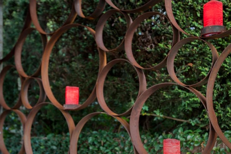 Authentic hand-rolled screening dividing areas in outdoor living spaces. Flat steel, hand-rolled with a rusted finish