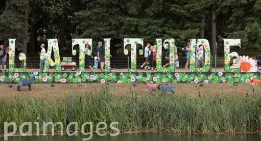 Festival goers walk past a big 'Latitude' sign at the Latitude festival, held in Henham Park in Southwold, Suffolk.