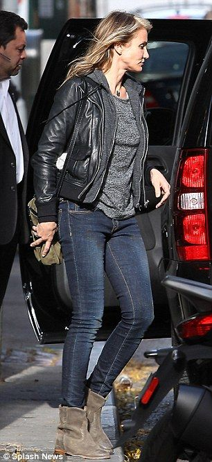 Casually chic: The make-up free 40-year-old layered up in a black leather jacket over a grey hoodie and marbled top for New York's 45-degree...