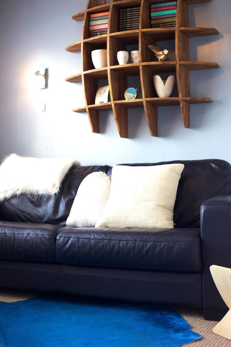 #cosy tv room. #leather couch #cube shelving #blue rug #Staging by Places and Graces.