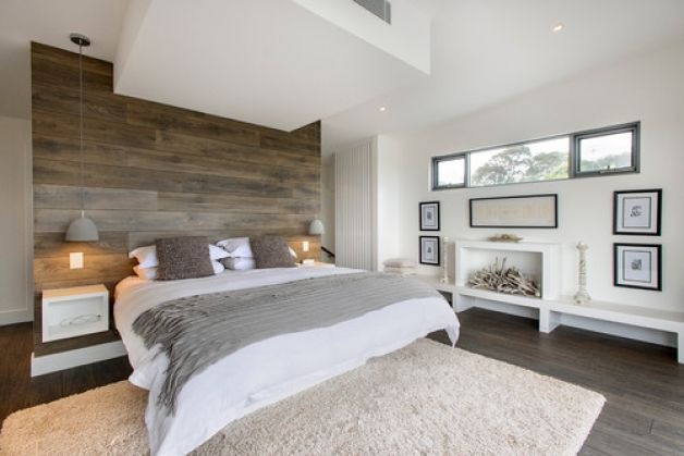 An accent wall made of a material that resembles driftwood creates a focal point in this restful bedroom. The designer plucked subtle accent...