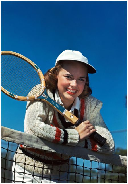 Smiling teen girl holdingtennis racquet leaning over tennis net 1948  Camerique