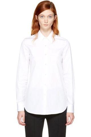 コットン ポプリンの長袖シャツ。カラーはホワイト。襟はスプレッド カラー。フロントはボタン開閉。シングルボタンのバレル カフス。同系色ステッチ。