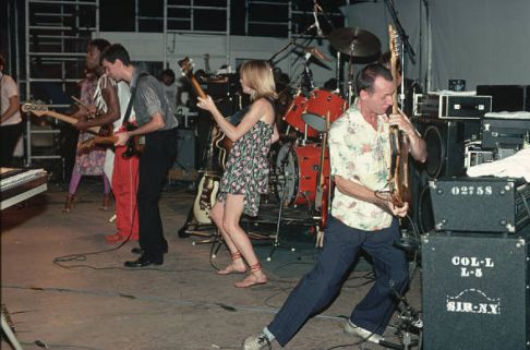 Talking Heads lead singer and guitarist David Byrne, bassist Tina Weymouth, keyboardist Jerry Harrison, and drummer Chris Frantz play a August 1980 concert in Central Park. Adrian Belew joins the original Talking Heads for the concert.