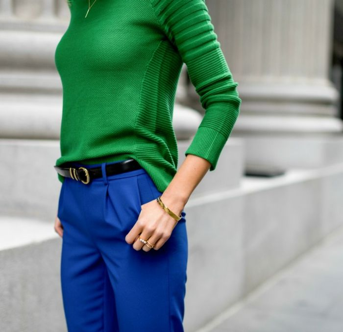 interview outfits for women, close up of female torso, wearing bright blue formal trousers, bright green sweater and black belt, delicate golden necklace rings and bracelet