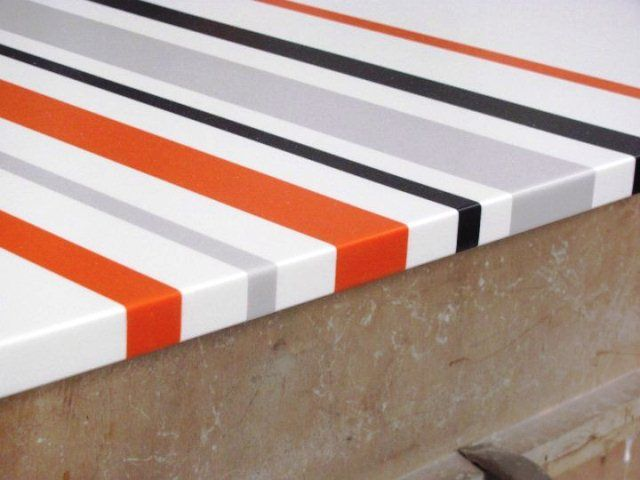Close up of corian tabletop with color inlays and logo for Local interior design firms