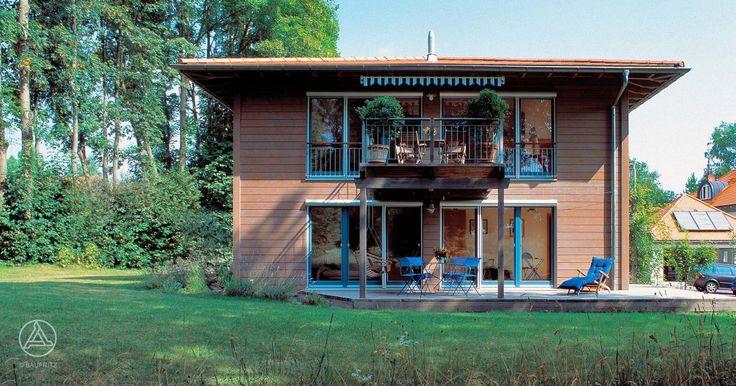 Gergraute Fassade mit taubenblauen Akzenten an Fenster und Türe. Die an 2 Seiten umlaufende Terrasse dient als Bindeglied zwischen Haus und großzuügigem Garten, viel Platz zum Wohlfühlen und Relaxen bieten die 2 Balkone, die auch für eine teilweise Überdachung der Terrasse sorgen. Baufritz Landhaus Sörgel-Bauer