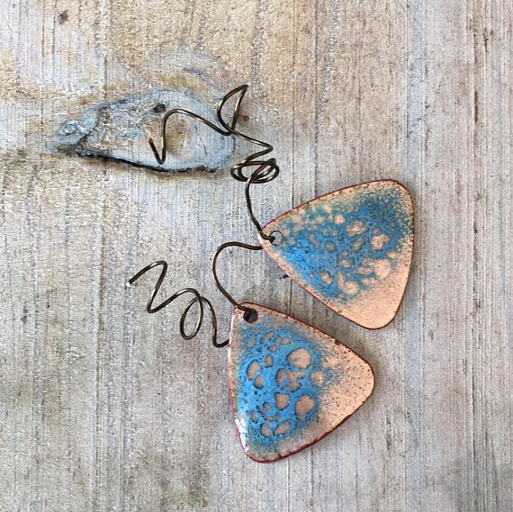Torch fired enamel copper charms or pendants, small guitar picks. They are slightly domed and topped with layers of vitreous enamel (glass). Aqua blue abstract pattern with a pebble effect to expose the underlying copper. The sides have been sanded and antiqued. This is the exact