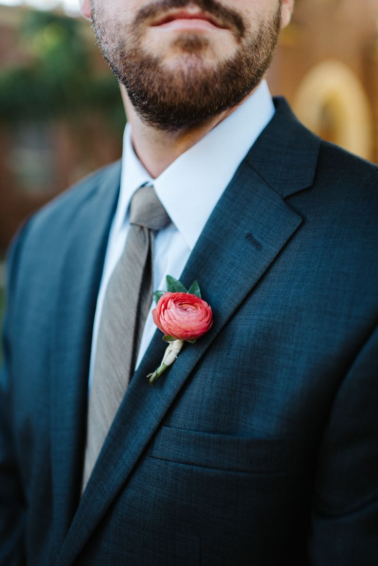 groomsman in a navy suit and grey tie wears a boutonniere of peach ranunculus & greenery wrapped in cream satin ribbon.