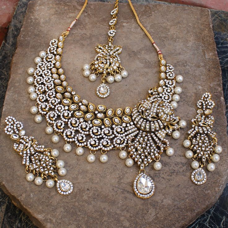 Wedding Bridal Necklace set with matching dangle earrings and tikka studded with Simulated White Cz Kundan and Faux Pearl Beads Gold Tone, handcrafted with high quality cz and kundan . Earrings - Measures (approx) (L)90mm x 30mm(W) OR 3 1/2