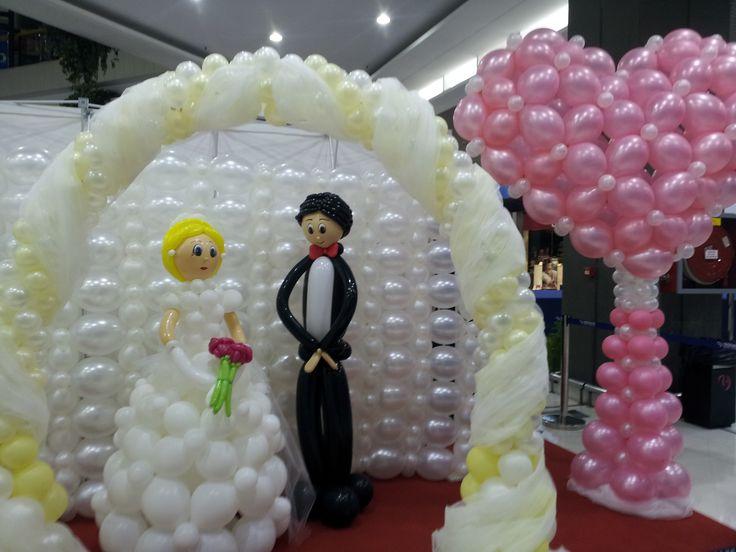 Novio con globos enmarcados en un arco con tul for Arreglos con globos para boda en jardin