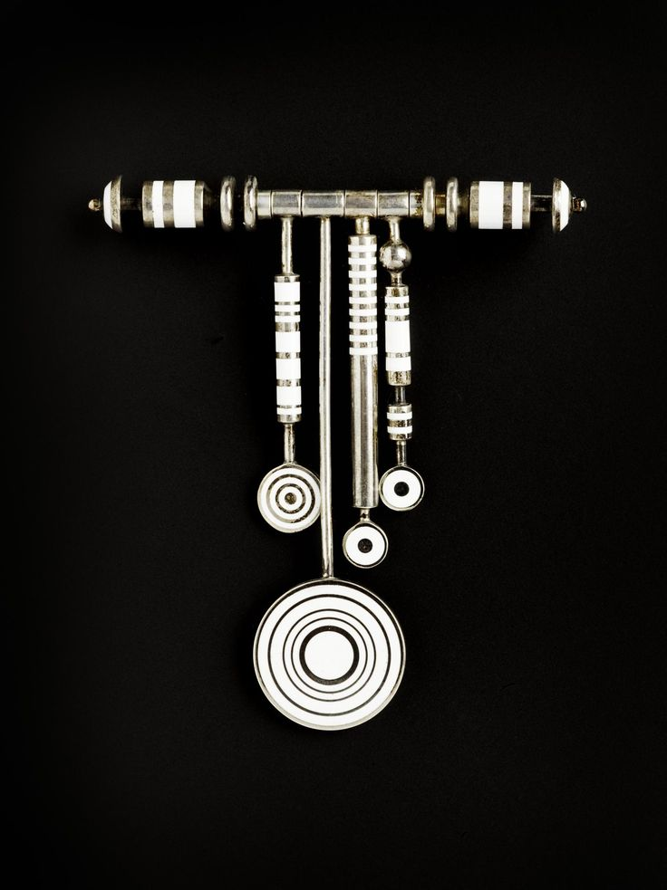 Brooch of silver and white enamel with bands round bars ending in discs: English, London, by Wendy Ramshaw, 1972