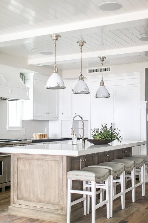 Three white enamel industrial pendants hang from a white plank ceiling above a gray wash center island fitted with a white quartz countertop finished with a sink and polished nickel pull down faucet.