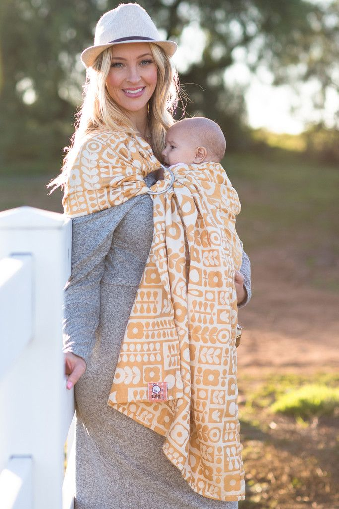 Baby Tula's Lubniki Sunflower - Wrap Conversion Ring Sling Baby Carrier. Shine bright in a cheerful, new colorway of our Tula woven, 'Lubniki'! It has flowers, petals and birds reinterpreted into a geometric block pattern that retains a sweet, nostalgic feel while appearing chic and modern. 'Lubniki' Sunflower ring slings provide a uniquely breathable support for babies, small and large. Available in various sizes 'Lubniki' can be worn by variety of body types.