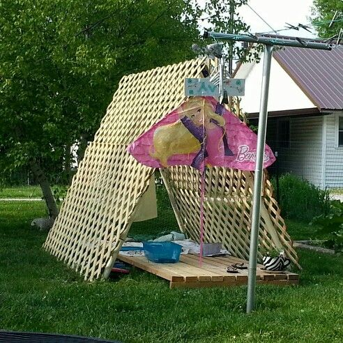 """Repurposed swing set int """"green"""" kids club house.  Remove swings and slide, attach 4 4x8 ft sections of treated lattice, attach with zip ties. Completely close off one end of the swing by cutting chicken wire to fit and folding in sharp ends, attach with more zip ties.  We added a deck to keep things off of the ground and to make it look homey. We used 10ft long 2x4's that we nailed onto a frame that our roofing materials were delivered on, knowing we could use it eventually for something…"""