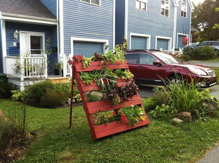 porte-plantes diy en palettes Euro repeintes en rouge dans le jardin