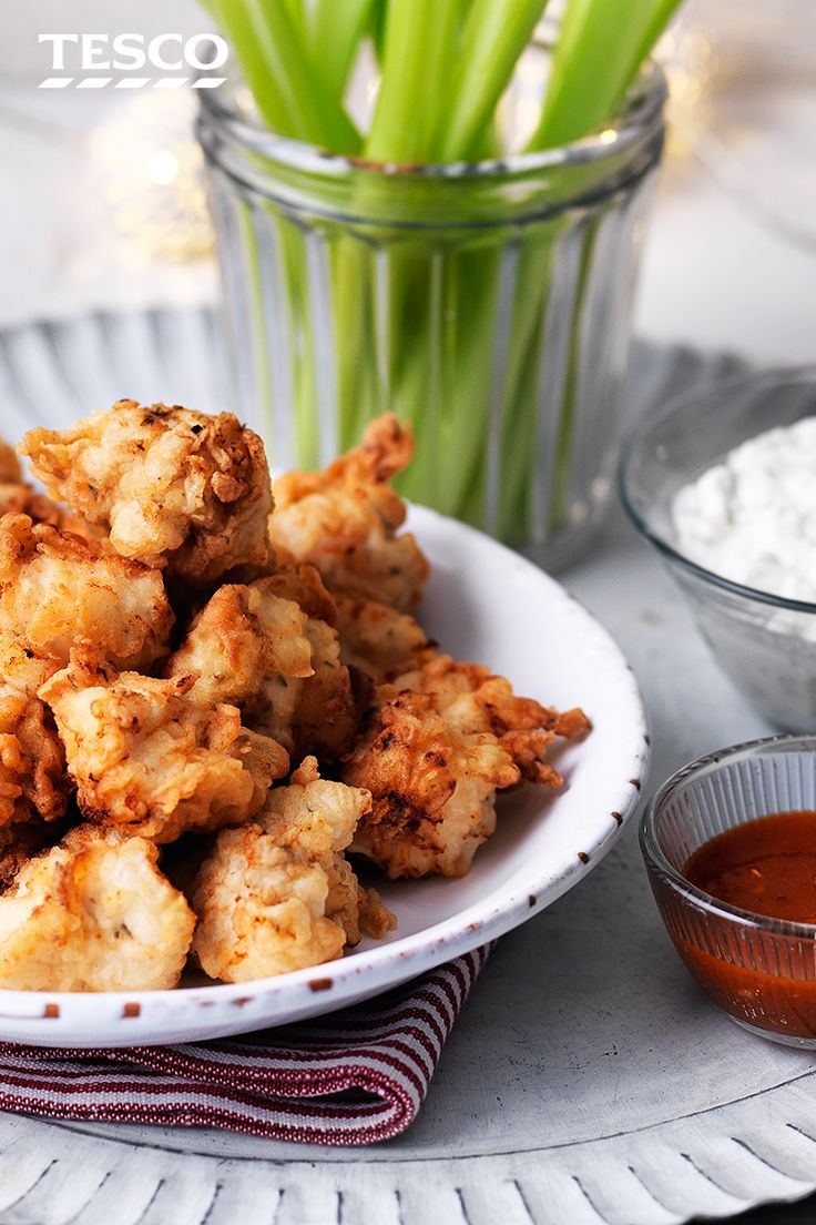 As party food ideas go, our popcorn chicken recipe is guaranteed to be a hit - buttermilk-marinated and lightly fried chicken is served with a blue cheese dip, cayenne pepper sauce and celery sticks. | Tesco