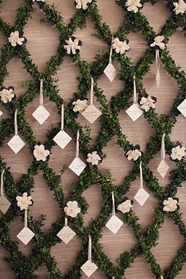 Escort Cards on garland  A unique escort card wall was embellished from natural boxwood garlands that created a pretty lattice design that framed the entrance to the ballroom. Pretty floral and guest cards were displayed.