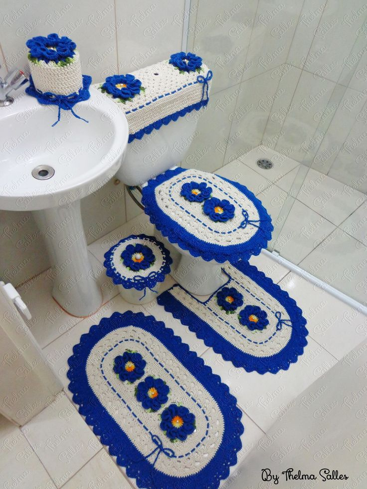 01 jogo de banheiro confeccionado com barbante crú e barbante azul com flores centrais contendo 06 peças: <br> <br>01 tapete de banheiro <br>01 tapete frente do vaso <br>01 tampa do vaso <br>01 tampa da lixeira <br>01 porta papel higiênico unitário <br>01 capa para caixa acoplada