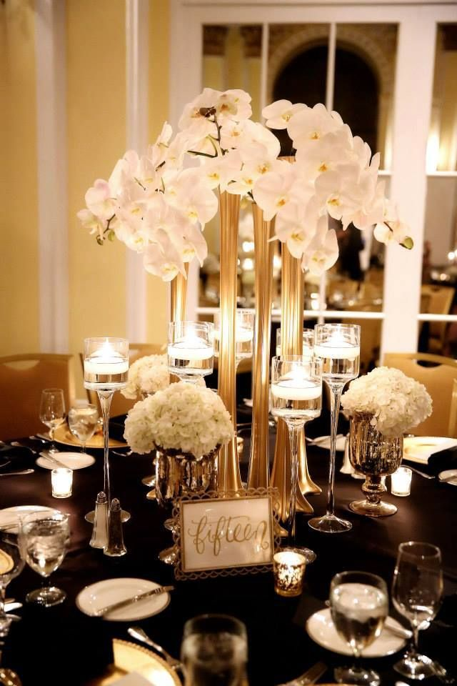 "Modern ""Great Gatsby"" styled elevated centerpiece featuring white phalaenopsis orchids with romantic candlelight and gold accents. Floral design by Modern Day Events + Floral. Photography by Karyn May Photography."