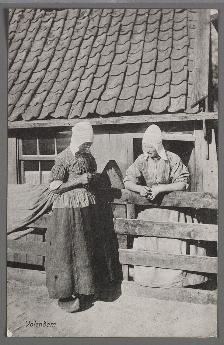 Twee vrouwen in dracht praten bij het hek voor het huis. 1900-1908 #NoordHolland #Volendam