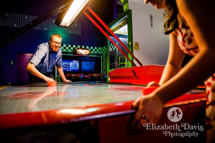 Couple+plays+air+hockey+at+arcade+engagement+session+|+Unique+engagement+photos+|+Elizabeth+Davis+Photography+|+Wedding+Photographer