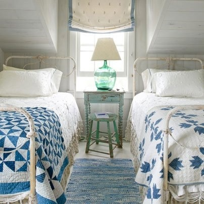 Twin beds with coordinating, not matching, quilts (Via Country Living Magazine Facebook Page)