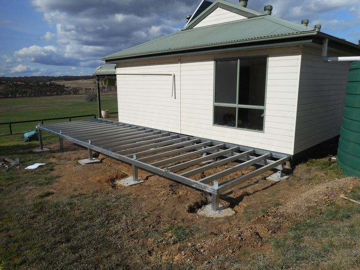 a steel deck frame over ezipiers will add some outdoor living space to this country home