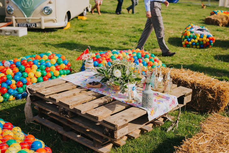 DIY seating and tables at this festival wedding. Photo by Benjamin Stuart Photography #weddingphotography #cratetable #haybales #tablescentres  #festivalwedding #outsidewedding #DIYwedding #creativewedding
