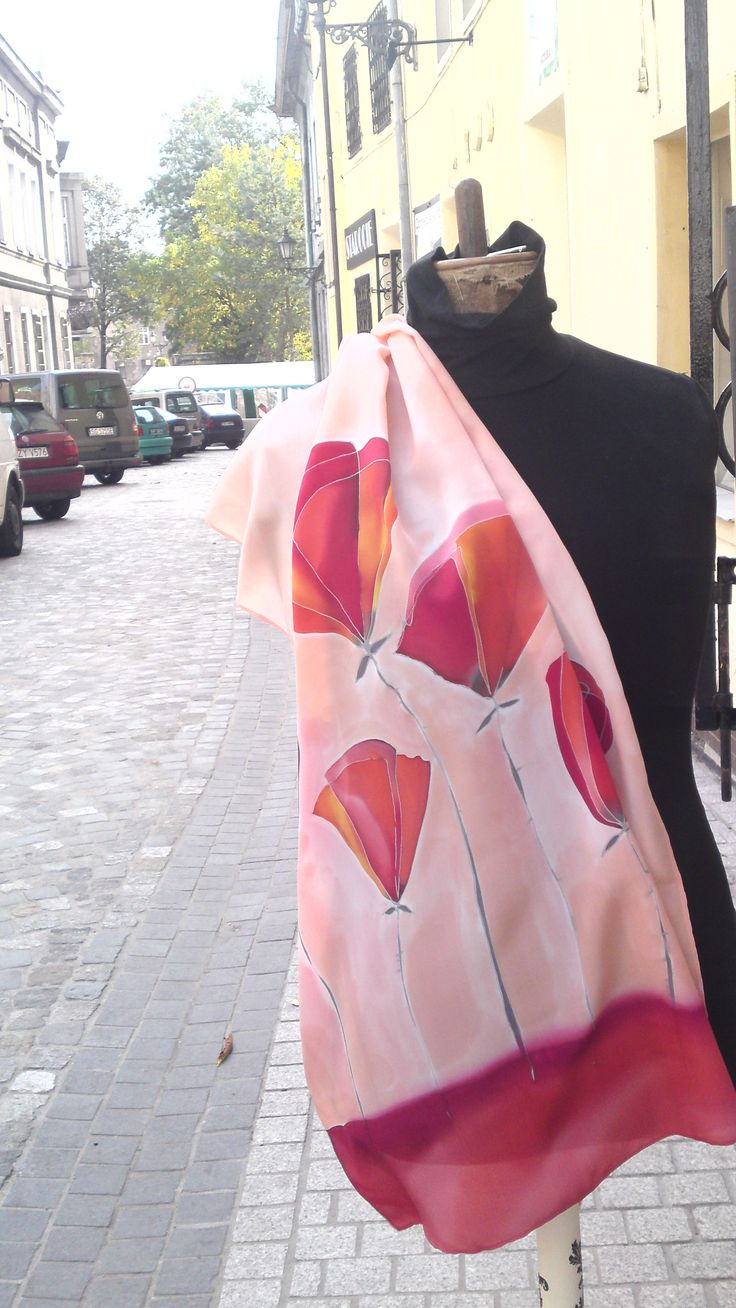 Coral red silk scarf, poppy flowers in brick and clay reds. Presented on bust outside of my workshop. Scarf is put around right elbow, looks good for show but not that practical as a way of wearing . Its covering right side of torso, you can see scarf theme very well. Hand painted by SilkAgathe.
