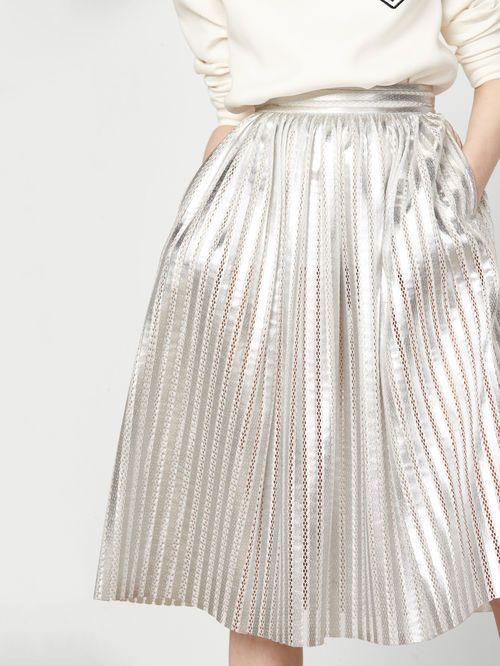 Jupe en maille basket métallisée JAURES. Confectionnée dans une maille basket métallisée, la jupe taille haute est pourvue: d'une large ceinture, de poches fendues sur les côtés, d'une fermeture zippée au dos ainsi que d'une fine doublure en jersey ton sur ton sur la partie haute. Elle sera idéale par-dessus un large sweat en néoprène pour une allure chic et décontractée résolument moderne!